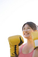 An ecstatic woman wearing her boxing gloves seen under the sky