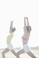 Two young women stretch their arms and legs as they exercise together