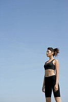 A side view of a woman in workout suit seen under the sky