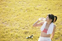 A young woman drinks water as she sits amidst grassland after her workout