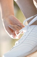Close up of white sports shoe is seen as one person ties the shoelace (thumbnail)