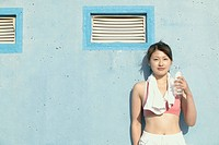 A young woman holds the bottle of water as she stares at the camera (thumbnail)