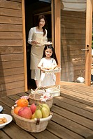 A small girl helping her mother to place meal on the wooden table