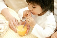 A small boy drinking juice with the help of a straw