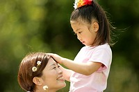 A young girl putting flowers in the hair of her mother