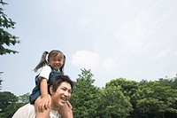 A girl riding her father's shoulders
