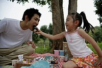 A daughter feeding a rice ball to her father