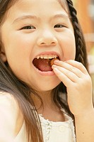 A portrait of a small girl eating chocolate (thumbnail)