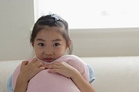 A girl holding a cushion on sofa (thumbnail)