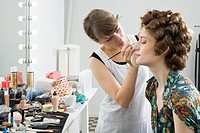 A make_up artist applying make_up on a model
