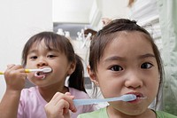 Sisters brushing teeth