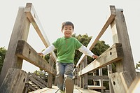 A small boy moving a step forward on the bridge