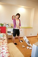 A young woman in cropped pants, vacuuming her room