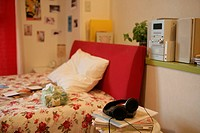 Music system, headphones and books seen at one corner of the bedroom near the bed