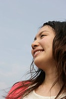 A young woman is seen under the sky as she smiles heartily