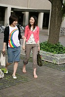 Two young women walking side_by_side