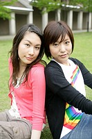 Two young women rest on each others back as they sit on the grassland