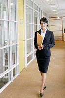 A businesswoman holding a file walks along the passage of the office