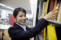 A woman smiles at the camera while finding a file from the shelf