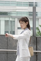 A woman looking at her watch as she is on her way (thumbnail)
