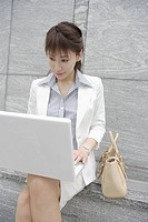 A woman working on her laptop with a bag beside her