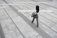 A rear view of a woman walking on a broad pathway