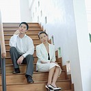 Low angle view of a businesswoman and a businessman sitting on a staircase