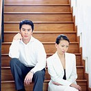 Businesswoman and a businessman sitting on a staircase (thumbnail)