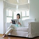 Businesswoman sitting on a couch reading a newspaper (thumbnail)