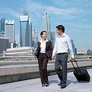 Low angle view of a businesswoman talking to a businessman and pulling a suitcase