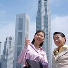 Low angle view of two businesswomen smiling in front of buildings