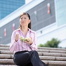 Close_up of a businesswoman holding a bowl of salad