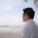 Side profile of a mid adult man standing on the beach