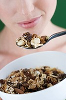 A young woman eating a bowl of muesli, close-up (thumbnail)