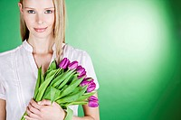 A young woman holding a bunch of purple tulips, smiling