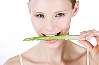 A young woman with a piece of asparagus in between her teeth