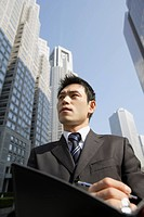 Businessman with office buildings, portrait