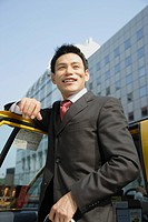 Man leaning against car door, portrait (thumbnail)