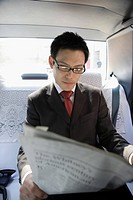 Businessman reading newspaper in car, portrait