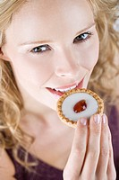 A portrait of a young blonde woman eating a cake with a cherry on top