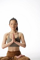Front view of a young woman meditating in lotus position (thumbnail)