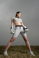 View of a young woman standing with boxing gloves (thumbnail)