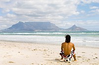 Young boy sitting on soccer ball on beach watching Table Mountain, Table View, Cape Town, Western Cape Province, South Africa