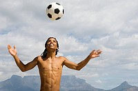 Young boy playing with soccer ball, Table Mountain in background, Table View, Cape Town, Western Cape Province, South Africa