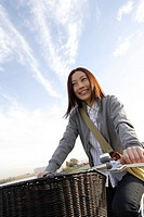 View of a young woman sitting on a bicycle