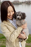 View of a young woman holding pet dog