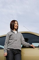 View of a young woman standing beside a car