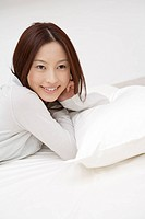 Side view of a cheerful woman lying on the bed