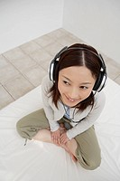 View of a young woman using a headphone