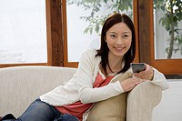 View of a young woman holding a remote control (thumbnail)